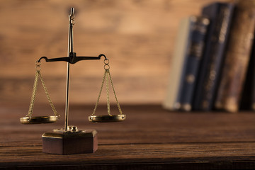 Golden scales of justice, gavel and books on brown background Law code, gavel and books