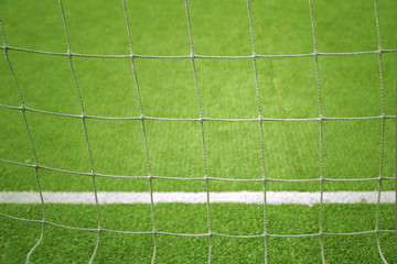 Wall Murals Air photo Soccer goal net closeup with blurred soccer field background. Selective focus used.