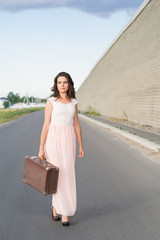 young woman with a suitcase on the road