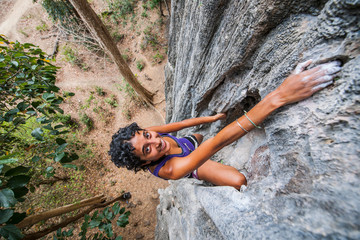High angle portrait of young woman sport climbing rock face, Thakhek, Khammouane, Laos