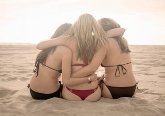 Rear view of three women wearing bikinis sitting on Santa Monica beach, California, USA
