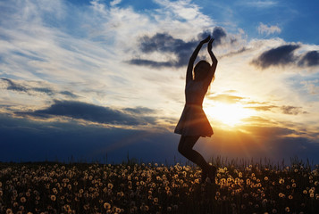 Happy woman jumping against sunset