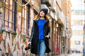 Young female photographer strolling along graffiti alley