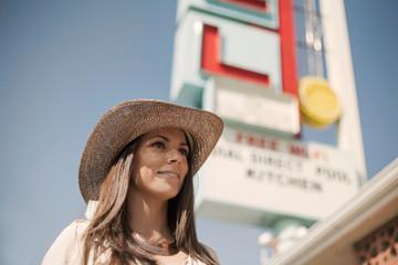 Female tourist waiting outside motel, Los Angeles, California, USA