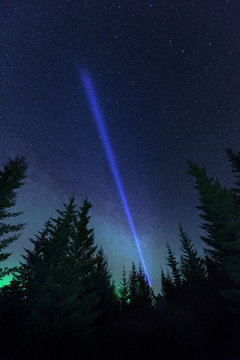 Laser beam and aurora borealis over forest, Thingvellir, Iceland