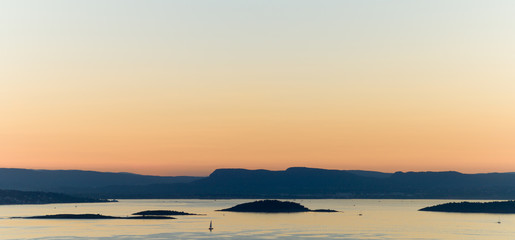 Lonely sailboat in the golden evening twilight.
