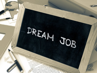 Dream Job Handwritten on Chalkboard. Composition with Small Chalkboard on Background of Working Table with Ring Binders, Office Supplies, Reports. Blurred Background. Toned Image. 3D Render.
