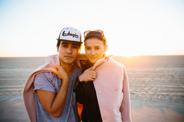 Portrait of young couple wrapped in overcoat on beach, Venice Beach, California, USA