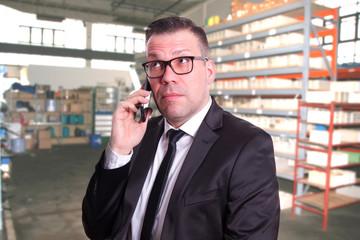 Geschäftsmann im Warenlager mit fragendem Blick am telefonieren