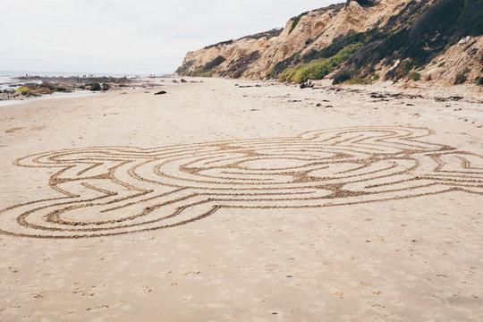 Line drawing pattern drawn onto beach sand, Crystal Cove State Park, Laguna Beach, California, USA