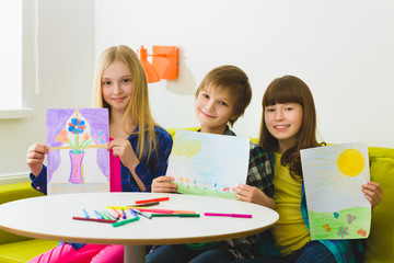 happy children show their pictures drawn. Indoor at room
