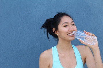 Young Asian female drinking a bottle of water