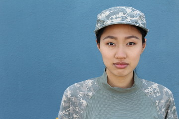 Portrait of serious female army soldier against blue background