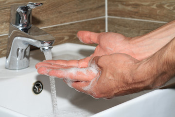 Hygiene concept. Man washing hands close up