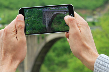 Man taking photo of mountain bridge / scenic landscape with mobile cell phone. Active holiday vacation, travel concept