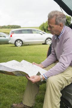 Man sitting on car boot reading map