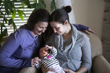 Baby girl sitting with mother and grandmother
