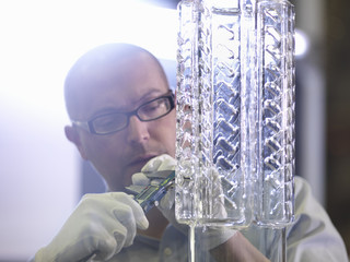 Worker performing quality control checks in glass factory