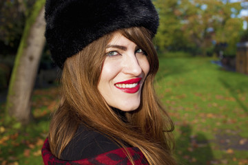 Portrait of woman wearing red lipstick and black hat