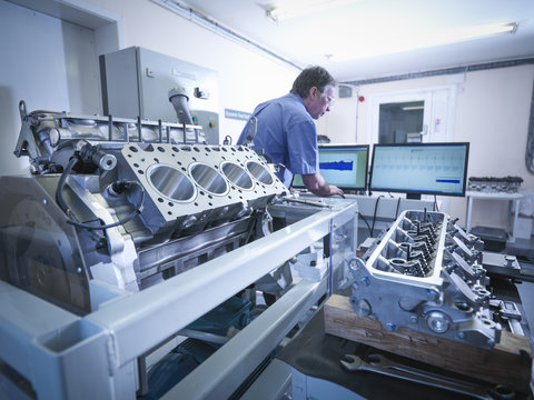 Engineer inspecting automotive engine in test facility