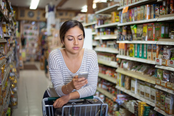 Young woman shopping with smartphone in health food store