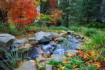 Colourful decorative waterfall in a beautiful autumn garden