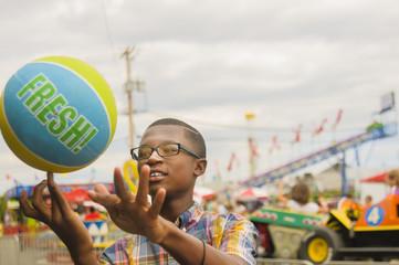 Teenage boy spinning basketball on finger at amusement park