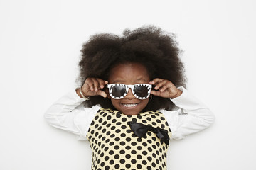 Girl wearing polka dot dress and sunglasses, close up