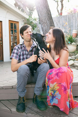 Young couple sitting on patio with dog licking face