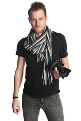 Attractive photographer with a digital slr camera, wearing a black tshirt, scarf and jeans. Standing against a white background.