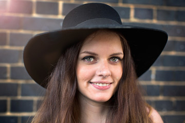 Portrait of young woman with hat and nose ring stud