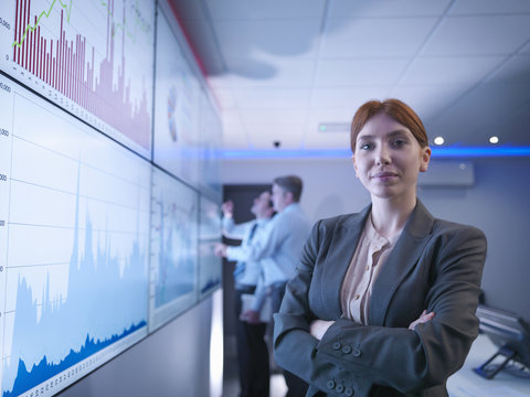 Businesswoman in front of graphs on screen in meeting room, portrait