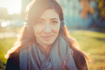 Portrait of mid adult woman listening to headphones in park