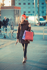 Mid adult woman wearing red pom pom hat strolling with shopping bags