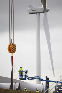 Workers installing wind turbine
