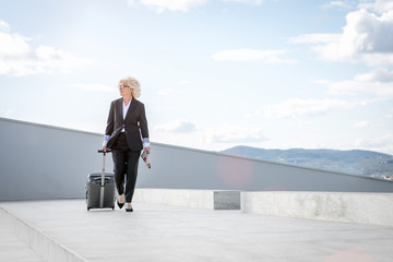Mature businesswoman walking with suitcase