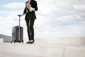 Mature businesswoman walking with suitcase, low section