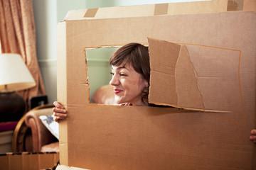 Mid adult woman peeking out of cardboard box window in living room