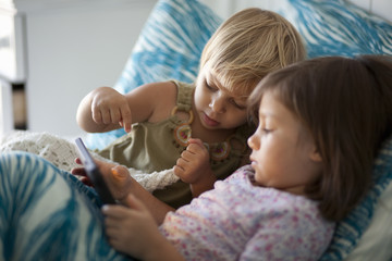 Girl and toddler sister sitting up in bed using digital tablet