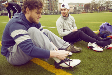 Soccer players tying sneaker laces on the soccer pitch