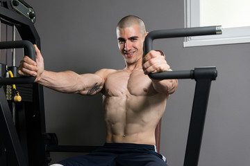 Young Man Exercising Chest In The Gym