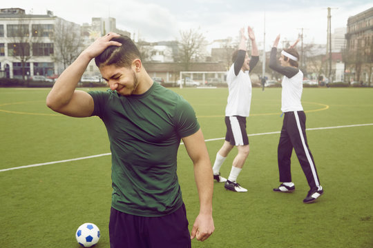 Disappointed male soccer player with hand in hair on soccer pitch