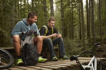 Two young men with mountain bikes, in forest, taking a break