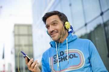 Smiling mature man choosing headphone music on smartphone