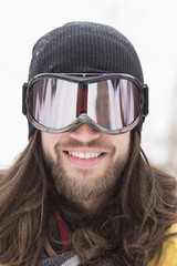 Close up portrait of smiling male snowboarder on street