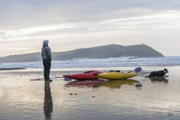 Young woman on beach with sea kayaks, Polzeath, Cornwall, England