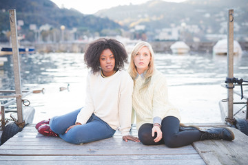 Portrait of two female friends sitting on pier, Lake Como, Italy