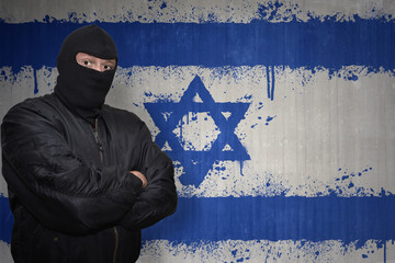 dangerous man in a mask standing near a wall with painted national flag of israel