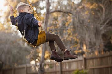 Young boy swinging high on garden swing
