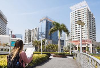 Rear view of young female tourist reading map, Macau, Hong Kong, China